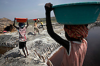 Children carry basins of salt at Lake Katwe.