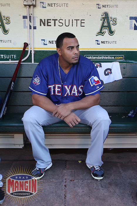 OAKLAND, CA - JULY 17:  Nelson Cruz #17 of the Texas Rangers gets ready in the dugout before the game against the Oakland Athletics at O.co Coliseum on Tuesday, July 17, 2012 in Oakland, California. Photo by Brad Mangin