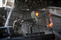 In this Sunday, Nov. 04, 2012 photo, a rebel fighter belonging to the Qatebee Sokor Al-Islam fires a machine gun over a building where Syrian troops loyal to President Bashar Al-Assad hide while they attempt to gain terrain forward the rebel lines during heavy clashes in the nearby Qastal Al-Harami battlefield in the Jdeide district of Aleppo, the Syrian's largest city. (AP Photo/Narciso Contreras).