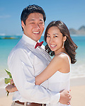 Asian bride and groom pose as the couple strolls on Lanikai beach - they look forward to their life as a married couple following their wedding.