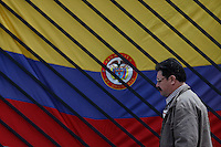 BOGOTA, Colombia. 13th June 2014. A Man walks pass the Colombian Flag on a street during presidential elections day in Bogota, Colombia. Photo by Eduardo Munoz Alvarez/VIEWpress