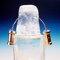 WEIGHTED WIRE CUTS THROUGH BLOCK OF ICE (1 of 4)<br /> Regelation of Ice<br /> The pressure exerted on the ice by the weighted wire lowers the melting point of ice causing it to liquefy under the wire.  As the wire passes thru, the ice refreezes behind it.  Wire is 1/4 thru the ice.