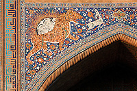 """Detail of solar tiger mosaic, Sher-Dor Madrasah, 1619-36, Samarkand, Uzbekistan, pictured on July 15, 2010 at sunset which lights up the elaborately tiled facade. The Sher-Dor Madrasah, commissioned by Yalangtush Bakhodur as part of the Registan ensemble, and designed by Abdujabor, takes its name, """"Having Tigers"""", from the double mosaic (restored in the 20th century) on the tympans of the portal arch showing suns and tigers attacking deer. Samarkand, a city on the Silk Road, founded as Afrosiab in the 7th century BC, is a meeting point for the world's cultures. Its most important development was in the Timurid period, 14th to 15th centuries. Picture by Manuel Cohen."""