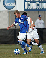 Creighton University midfielder Zach Barnes (12) dribbles under pressure..NCAA Tournament. Creighton University (blue) defeated University of Connecticut (white), 1-0, at Morrone Stadium at University of Connecticut on December 2, 2012.