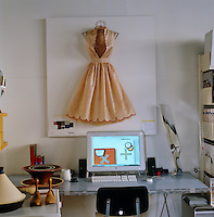 A satin 1950's style dress is displayed on a pinboard on the wall in this home office