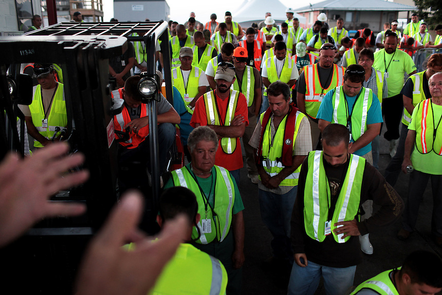 Local fishermen bow their heads in prayer before leaving to pick up hard boom for BP on August 24th.