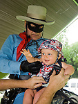 Photo by Phil Grout..&quot;Hey, Dad.  Who is this masked man, anyway?&quot;  Nine-month-old .Macyn Vanderwoort of Reisterstown seems to be having a ball while.&quot;The Lone Ranger&quot; and Dad wrestle to get this little doggie up.in the saddle.  &quot;The Lone Ranger&quot; visited the American Legion Post 200 in Hampstead to celebrate the American flag and commemorate the.66th anniversary of D-Day.