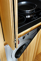 In the kitchen sliding doors conceal the hob and the washing machine below it