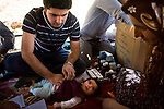 Dr. Kamal Kadr examines 6-week-old Pais Rasul Hasan while her mother Khadija Abdullah watches in a refugee camp near the villages of Sharkhan and Ali Rash, Iraq, near the border with Iran, June 12, 2010. The doctors treated the refugees for chest and stomach infections and chronic health issues like hypertension. Residents of the two villages became refugees when shelling from Iran made staying in their homes too dangerous. Iranian soldiers reportedly set up outposts inside the borders of Iraqi Kurdistan, raising questions about Iraq's ability to secure its borders.
