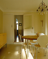 A charming note of frivolity comes from a vintage chandelier in this otherwise plain and simply furnshed dining room