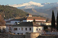 View of buildings in Granada seen from the San Cristobal viewpoint, and in the foreground, the Muralla de la Alcazaba, an 8th century wall protecting El Albayzin, the medieval Moorish old town of Granada, Andalusia, Southern Spain. In the distance are the snow-capped peaks of the Sierra Nevada. Picture by Manuel Cohen