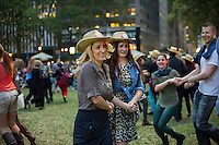 Hundreds of New Yorkers and visitors dance up a storm in Bryant Park in New York on Wednesday, September 25, 2013 during the third and last square dancing session of the year in the park. As incongruous as it sounds square dancing's popularity in New York ebbs and flows with it reaching its peak after World War II where thousands would participate in large dances held in Central Park. (© Frances M. Roberts)