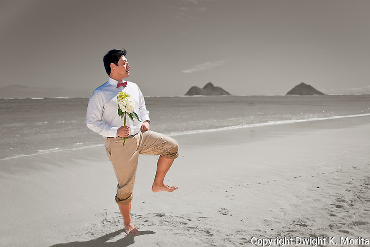 Asian groom goofs around with a Captain Morgan pose while waiting for his bride with a bouquet of flowers. Husband poses during a stroll on Lanikai beach as they look forward to their life as a married couple following their wedding. Color and BW cutout
