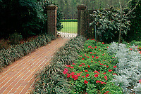 Maclay gardens gate with brick walkway and iron gate with blooming petunias, Tallhassee, Florida