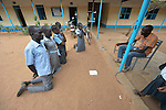 Forced to kneel in the dust, students are disciplined by a teacher at the John Paul II School in Wau, South Sudan.