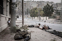 Rebel fighters drag themselves on the street as they carry out a rescue mission of one Syrian civilian whom was shot twice, at his stomach and at his back, by one Syrian army sniper while was walking at the front line in Bustan Al-Bashar, northeast of Aleppo City.