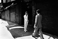 USA. New York City. Spanish Harlem. Carlos (R) meets his friend Chino( L) in the street. Both teenagers wear their sunday best clothes for their religious confirmations. They are about to shake hands. Both Puerto Rican young men and their family live below the poverty line and receives public assistance (AFDC, Home Relief, Supplemental Security Income and Medicaid). Spanish Harlem, also known as El Barrio and East Harlem, is a low income neighborhood in Harlem area. Spanish Harlem is one of the largest predominantly Latino communities in New York City. 20.04.86 © 1986 Didier Ruef .