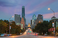 Looking down Congress Avenue, this image shows a portion of the downtown Austin skyline. At the end of the street is the Texas State Capitol on an early November morning.