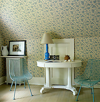 A painted side table and a pair of 1960's  blue wire chairs sit beside a cupboard door built into the eaves