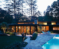 The illuminated Modernist property is viewed from the paved terrace surrounding the outdoor swimming pool