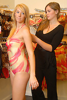 Fit Specialist Blair Friley helps Lindy Waddel try on a one piece holter by Luxe at SwimSpot at the Santa Monica Place Mall on Thursday, March 22, 2012.