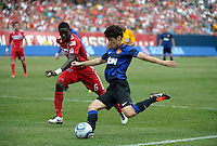 Manchester United midfielder Ji-Sung Park (13) launches a shot while being defended by Chicago Fire defender Jalil Anibaba (6).  Manchester United defeated the Chicago Fire 3-1 at Soldier Field in Chicago, IL on July 23, 2011.
