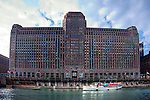 A tour boat passes below the famous Merchandise Mart building in Chicago, IL.