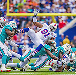 14 September 2014: Buffalo Bills defensive end Manny Lawson (91) cartwheels over players on a punt return in the first quarter against the Miami Dolphins at Ralph Wilson Stadium at Ralph Wilson Stadium in Orchard Park, NY. The Bills defeated the Dolphins 29-10 to win their home opener and start the season with a 2-0 record. Mandatory Credit: Ed Wolfstein Photo *** RAW (NEF) Image File Available ***
