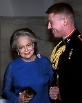 Actress Olivia de Havilland is escorted by an unknown Marine at the White House on February 28, 1994.