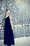 A young woman with pale skin dressed in a black gown standing next to a lake in a snowy forest.