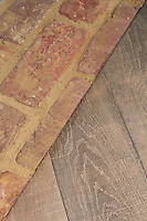 Detail of the meeting of brick flooring with wood floorboards in the kitchen