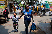 Razia Shabnam (in blue) picks her son, Saihaan, up from the St. Thomas School in Kidderpur after finishing her boxing training sessions in Calcutta, West Bengal, India. Razia Shabnam, 28, was one of the first women boxers in Kolkata. She was also the first woman in her community to go to college. She is now a coach and one of only three international female boxing referees in India.  Photo by Suzanne Lee for Panos London