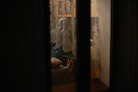 A woman in her kitchen through a lace curtain in Odessa, Ukraine on January 6, 2016.