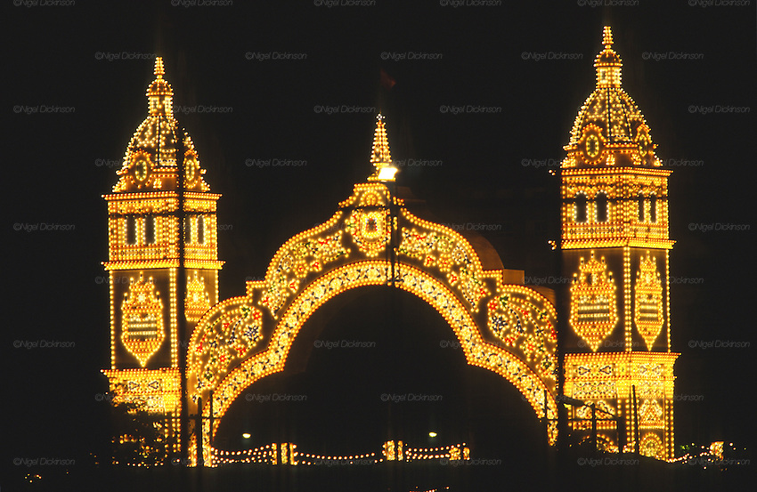 "The colorful entrance archway to the Feria park, with all the casetas, is decoratively painted and illuminated at night..The Feria de abril de Sevilla, ""Seville April Fair"" dates back to 1847. During the 1920s, the feria reached its peak and became the spectacle that it is today. It is held in the Andalusian capital of Seville in Spain. The fair generally begins two weeks after the Semana Santa, Easter Holy Week. The fair officially begins at midnight on Monday, and runs six days, ending on the following Sunday. Each day the fiesta begins with the parade of carriages and riders, at midday, carrying Seville's citizens to the bullring, La Real Maestranza...For the duration of the fair, the fairgrounds and a vast area on the far bank of the Guadalquivir River are covered in rows of casetas (individual decorated marquee tents which are temporarily built on the fairground). Some of these casetas belong to the prominent families of Seville, some to groups of friends, clubs, trade associations or political parties. From around nine at night until six or seven the following morning, at first in the streets and later only within each caseta, crowds of people party and dance Sevillanas, traditional Flamenco dances, Sevillan style drinking Jerez sherry, or Manzanilla wine, and eating tapas. Men and women dress up in their finery, the traditional ""traje corto"" (short jacket, tight trousers and boots) for men and the ""faralaes"" or ""trajes de flamenca"" (flamenco style dress) for women. The men traditionally wear hats called ""cordobés""."