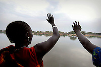 Women wave to people on the edge of the River Nile as they arrive in Bor on a barge returning Dinka tribespeople to their homeland after the civil war.  The resettlement programme is organised by the IOM (International Organisation for Migration).  Tens of thousands of Dinka tribespeople are among the estimated 3.8 million people displaced during the two-decade long conflict between the government and the SPLA (Sudanese People Liberation Army)...