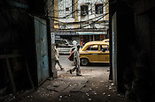 An old man walks past a dilapidated entrance of an old house in Kolkata, West Bengal, India.