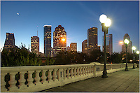 Early on an Autumn morning, the Sabine Street Bridge is quiet as the awakening Houston skyline rises in the distance. Images such as this are easy to find along Allen Parkway and the Buffalo Bayou. On this morning, the crescent moon was just climbing in the east, but the morning light illuminated the entire moon. <br />