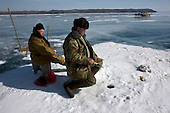 Amateur fishermen catch Omul fish -- a relative of the salmon -- through a hole in the ice in the frozen Lake Baikal in Siberia, Russia. .Baikal, the world's largest lake by volume, contains one-fifth of the earth's fresh water and plunges to a depth of 1,637 metres..The lake is frozen from November to April, allowing people to cross by cars and lorries.