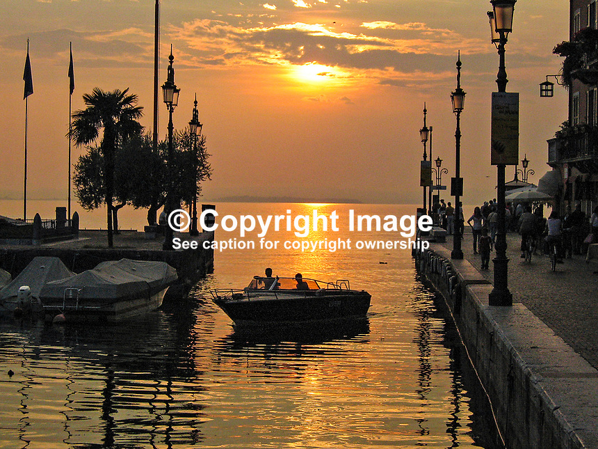 Italy, Lazise, harbour, opening unto Lake Garda, sunset, dusk, people, boats, 200609190278..Copyright Image from Victor Patterson, 54 Dorchester Park, Belfast, UK, BT9 6RJ..Tel: +44 28 9066 1296.Mob: +44 7802 353836.Voicemail +44 20 8816 7153.Skype: victorpattersonbelfast.Email: victorpatterson@mac.com.Email: victorpatterson@ireland.com (back-up)..IMPORTANT: If you wish to use this image or any other of my images please go to www.victorpatterson.com and click on the Terms & Conditions. Then contact me by email or phone with the reference number(s) of the image(s) concerned.