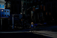 A woman walks a street during a sunny day in the Neighborhood of Exchange Place in New Jersey, 12/15/2015 Photo by VIEWpress
