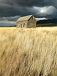 A leaning abandoned house in a Nevada field stands before an approaching storm.
