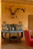 Antlers hang above a console table on which stands a pair of lanterns and a selection of objects