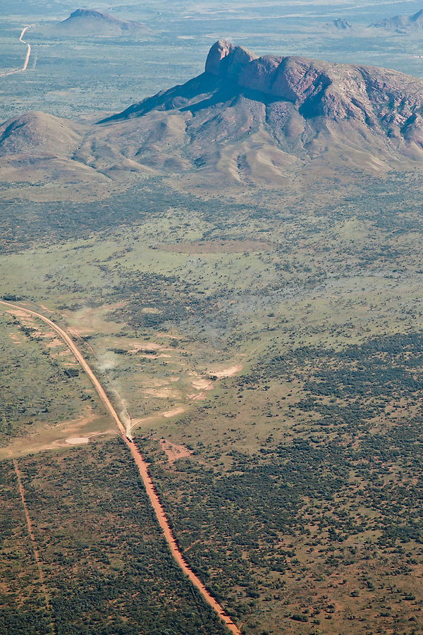 Aerial view of Haasts Bluff, between the remote indigenous  communities of Papunya and Haasts Bluff. A Road Train can be seen on the dirt road.