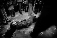 Ayacucho, Peru, Jan. 30, 2007 - A young girl collapses while dancing wildly in a makeshift Pentecostal church. Though unconscious and bleeding, the churchgoers continue to stand over her and chant. Churchgoer, Victor Samor said this was God's way of releasing evil spirits from her body. Though still the predominant religion in Peru, Catholicism has been on a steady decline since the country gained its independence from Spain. In the rural and poorer areas, many Peruanos have returned to their native religions or have found hope in Protestant religions.