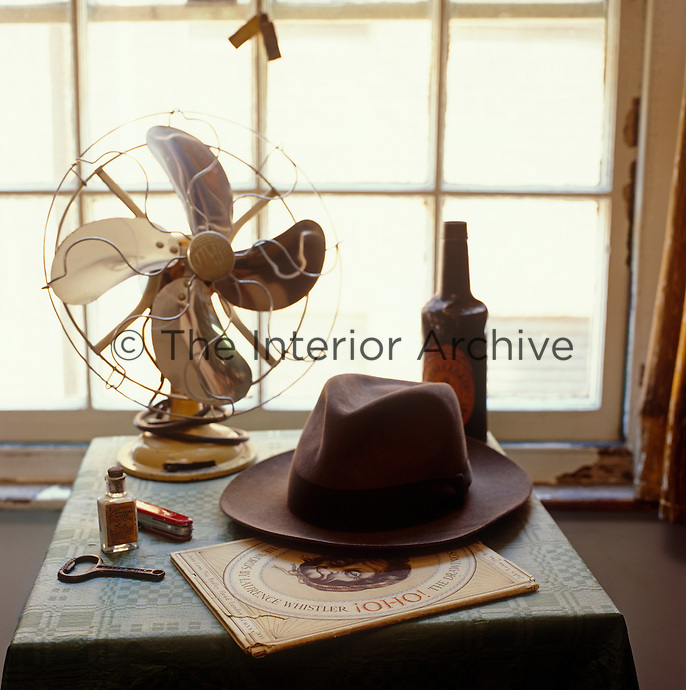 A vintage fan, a trilby and other masculine items are arranged on a bedside table