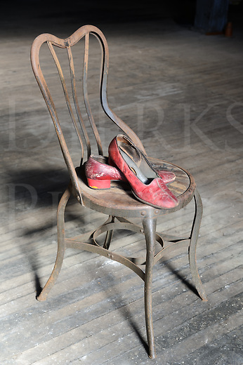Old and worn out red shoes on a rusty metal chair with a dirty wooden floor for a background, all alone after the last dance.