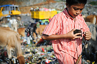 Taupik, 14, sharpening his picking tool at the 'Trash mountain', Makassar, Sulawesi, Indonesia.