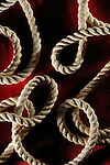 Artistic abstract pattern of rope twists on dark red background