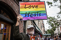 "NEW YORK JUNE 13: Man holds a banner with the Gay flag and a message ""Love Heals""  at the door of the Stonewall Inn, a historic gay bar in New York 13, 2016. People gather at a vigil in solidarity for the victims killed at Pulse nightclub in Orlando Photo by VIEWpress/Maite H. Mateo."