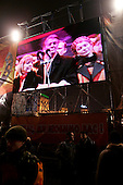 """Kiev, Ukraine.December 26, 2004..A pro-Viktor Yushchenko rally in Kiev as election polls close. He is joined on stage by his wife Kathy, two children as well as his political partner Yulia Timoshenko. ..Images of the stage are shown on two large screens set up at the ends of the stage...Supporters rally to support him as first election polls show him in a strong lead. ..The first round of voting was considered fraudulent when the ruling president Viktor Yahukovich won and the opposition candidate Viktor Yushchenko lost. ..Several hundred thousand Ukrainians took to the streets of Kiev and held daily rallies on Maidan Independence Square. The protests lasted nearly a month before the first vote was declared invalid and a new round of elections held on December 26, 2004. ..The demonstrations would come to be known as the """"Orange Revolution"""" after the color of the opposition party."""
